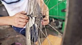 destruição : Teenage boy repairing the wheel of his bicycle in a workshop in a close up view on his hands Vídeos