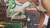 tokarka : Boy working on lathe machine, with focusing and concentrating, viewed in close-up from the side. Wideo