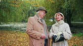 кошелек : Senior man and woman in elegant warm clothes cheerfully laughing while standing in wonderful autumn park together Стоковые видеозаписи