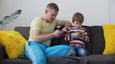 mobile game : devices in the life of a modern family. dad with a small son playing games on smartphones, sitting on the sofa at home.