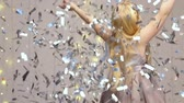beautiful blonde girl throws silvery confetti on the background of a blinking garland - slow motion