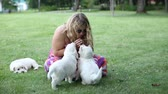 young woman playing with puppies of golden retriever in park