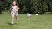 little blonde girl running around with puppies of a golden retriever in the park Стоковые видеозаписи
