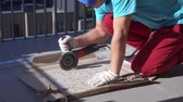 kachlová : Repair and decoration of apartments and houses. man cuts porcelain tile grinder on the terrace Dostupné videozáznamy