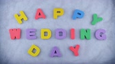 evlenmek : Words Happy Wedding Day appearing letter by letter on the blue texture for background. Different color letters. Stok Video