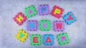 vykružovačka : Words Happy New Year made of alphabet puzzle appearing word by word with the blue texture for background. Different color letters. Dostupné videozáznamy