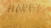 Words Happy Easter appearing word by word on the golden sandy beach. Letters are handwritten. Stok Video