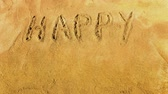 Words Happy Easter appearing letter by letter on the golden sandy beach. Letters are handwritten.