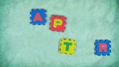 Message Happy Easter appearing randomly piece by piece of alphabet puzzle with the green texture for background Stok Video