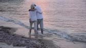 Couple in love walking on the sandy beach in the sunset