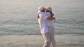 Happy couple running into each others arms and kissing on the sandy beach in the sunset Stok Video
