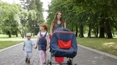 waggon : Family walking in the park - mother with a baby carriage and two children