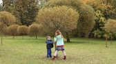 travessura : Children shaking a tree in the autumn park, leaves are falling