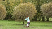 travessura : Little girl shaking a tree in the park, leaves are falling