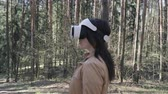 head mounted display : Brunette woman in vr headset standing in the forest and turning the head, steadicam shot, steadicam shot