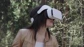 head mounted display : Brunette woman in vr headset standing in the park and turning the head, zoom out