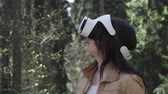 head mounted display : Close up brunette woman in vr headset standing in the park and turning the head