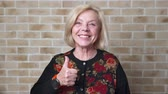 elation : Happy smiling senior woman showing thumbs up gesture, brick wall background Stock Footage