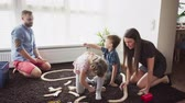 épít : Parents help their children to build a toy railroad on the floor in a room
