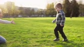 family love : Cute little boy runs to mother in embrace, spring park at sunset Stock Footage