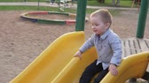 dětské hřiště : Cute little boy moving down from childrens slide in park