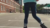 city lifestyle : Young woman rides on roller skates and whirl in city Stock Footage