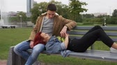 datas : Young happy couple holding hands and resting together on bench in city park