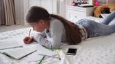 tankönyv : Little school girl studying at home lying on bed and writing in notebook