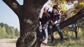 irmãs : Happy children sitting on big tree and carefree swinging legs on autumn day