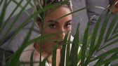 Beautiful sensual young woman with big eyes looking through leaves of plant