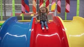 Happy girl moving down slide on playground in childrens center