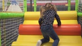 Girl climbs stairs and slides down on play ground in childrens center
