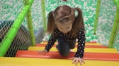 Child climbs stairs on playground in childrens center Stock Footage