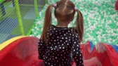 the game : Girl moving down slide on playground in childrens center