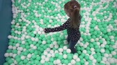 Girl walking on small balls in childrens play center