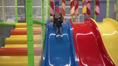 Happy kid moving down slide in childrens play center Stock Footage