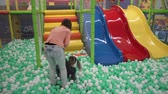 Mother and daughter walking on balls on playground in childrens center