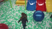 Little girl walking on small balls in childrens play center Stock Footage