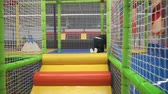 Happy little girl moving down slide on playground in childrens center Stock Footage