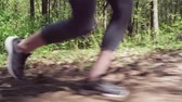 Legs of runner run on forest road