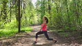 woman doing stretching before run in forest