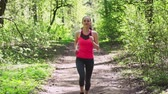 Fitness woman running in spring sunny forest