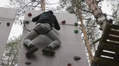 Man climbing on wooden wall in training camp for climbers in forest