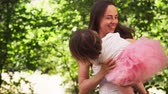 Mother hugs adorable baby and whirls with her in sunny summer park