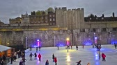winter : Twilight ice skating scene on the ice rink at Tower of London in the city of London, United Kingdom