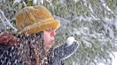 blow : Atractive teen in winter hat blowing snowflakes Stock Footage