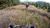j��zda na kole : An extreme mountain biker speeds down a  trail during the day. Downhill tracking shoot