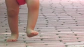 parent : Barefoot baby teaching her first steps to walk toward camera