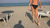 pegada : Man shadow following female model on beach chair standing up and walking toward water