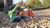 brother : Three children boy and girls play throwing leaves in autumn forest